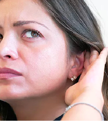 girl trying to listen with her hand behind her ear